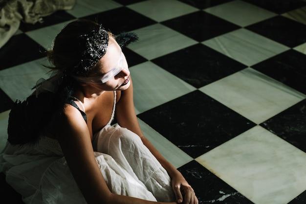 床に座っている目の束縛の女性