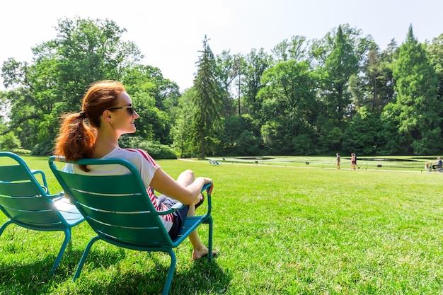 Женщина в очках расслабиться на зеленом поле.