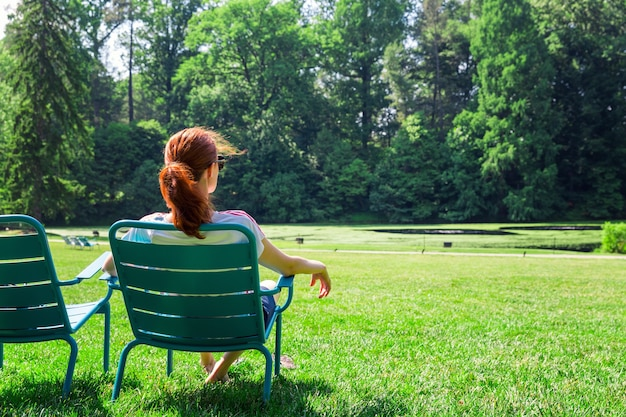 眼鏡の女性は、グリーンフィールドでリラックスします。