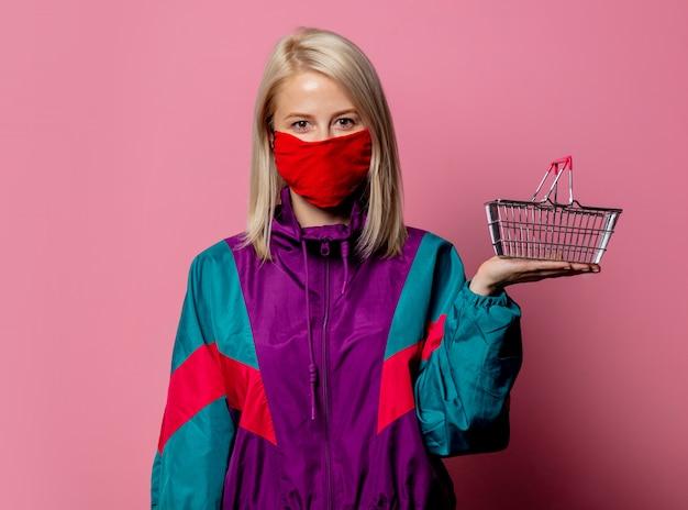 フェイスマスクとピンクのショッピングバスケットと80年代の服の女性