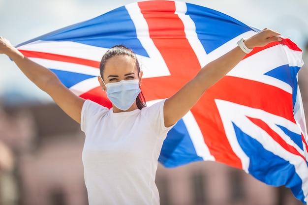 안면 마스크를 쓴 여성이 강력한 유지 캠페인 동안 영국 국기를 들고 있습니다.