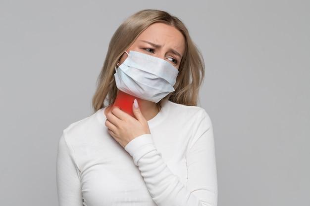 Женщина в маске почесывает шею