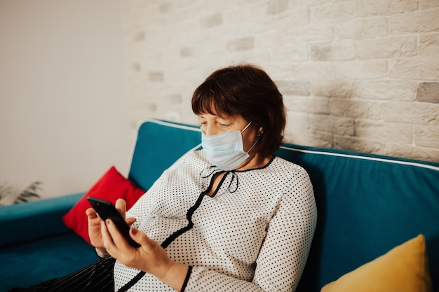 소파에 집에 앉아 의사를 호출 얼굴 마스크에 여자