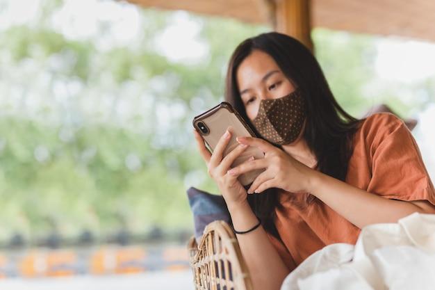 Женщина в маске, используя свой мобильный телефон, сидя в кресле.