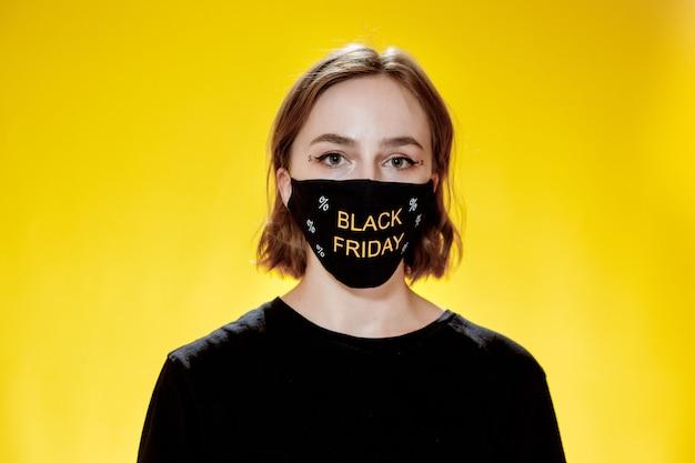 블랙 프라이데이 쇼핑백을 손에 들고 얼굴 마스크를 쓴 여자. 전염병 동안 판매. 검은 금요일 개념입니다.