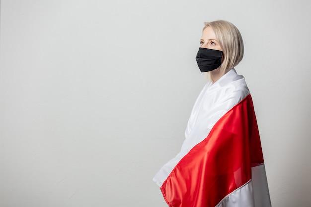 흰 벽에 전 벨로루시 국기와 얼굴 마스크에 여자