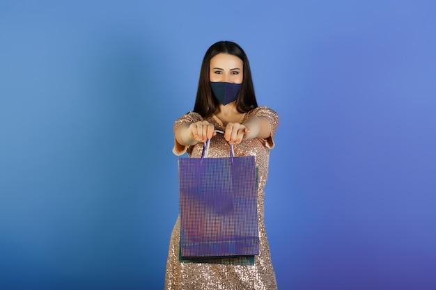 Женщина в маске с бумажными пакетами на синем