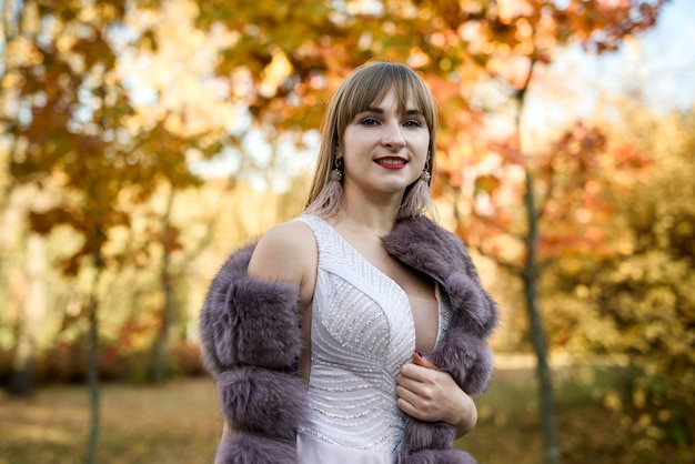 秋の風景の中でポーズをとってファッションベージュのドレスと毛皮のコートの女性。流行の服