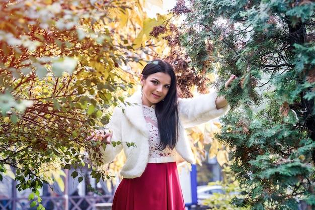 秋の公園でポーズをとってファッションドレスと毛皮のコートの女性