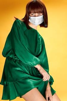 医療マスクウイルスcovid-19でポーズをとってファッションドレスを着た女性。
