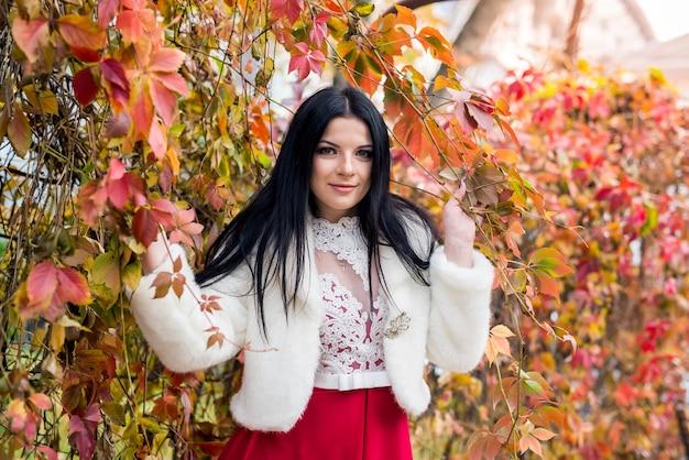 公園で黄色の葉でポーズをとってファッションドレスの女性