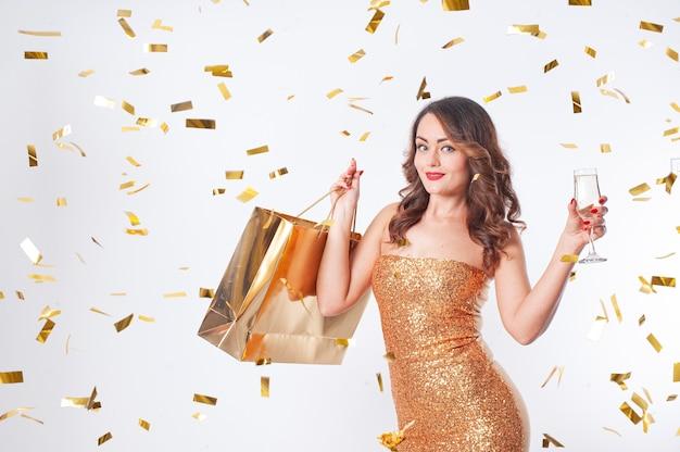 金色の紙袋とスパークリングワインのグラスとパーティーで祝う金色の紙吹雪、白いスタジオの背景を持つファッションの黄金の服の女性