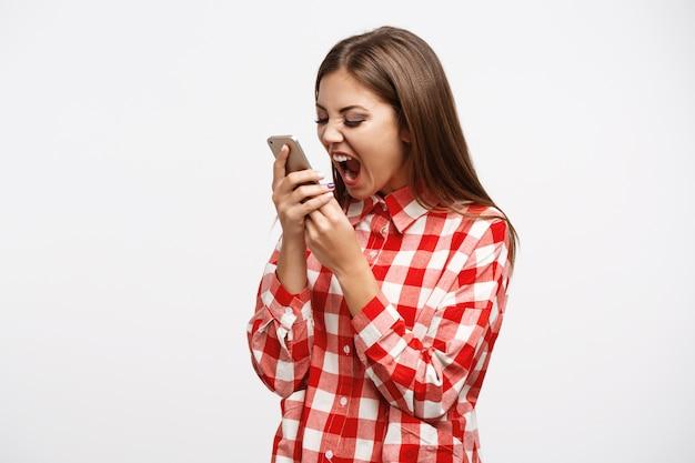 Женщина в моде весенний взгляд кричит на телефон, глядя безумный