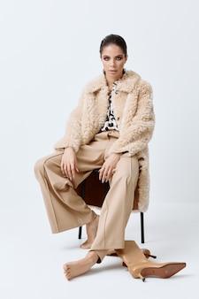 明るい化粧品をポーズするファッショナブルな服ベージュの毛皮のコートの女性。
