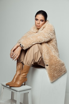 ファッショナブルな服の女性茶色のブーツ秋のスタイル