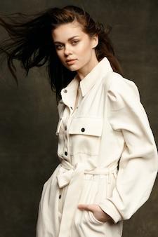 어두운 배경과 점프 슈트 스타일의 셔츠 모델에 유행의 옷을 입은 여자