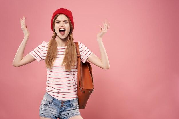 手でバッグをポーズするファッショナブルな服の女性モダンなスタイルのピンクの背景