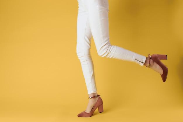 スタジオの黄色の背景をポーズするファッショナブルな服の靴の女性
