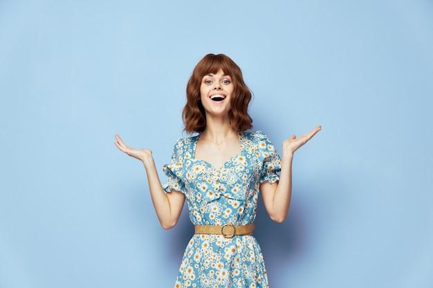 ファッショナブルなドレスの女性手ジェスチャー短い髪の夏服で陽気な笑顔