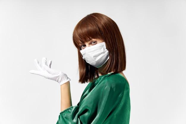Женщина в модном платье позирует в медицинской маске