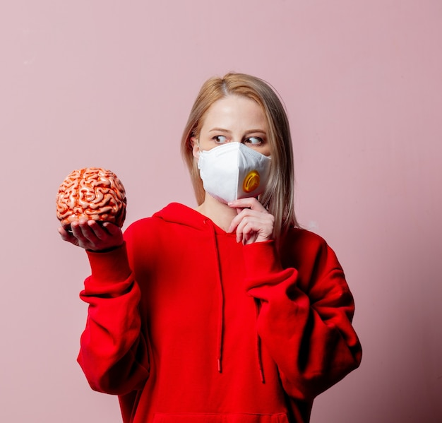 Женщина в стандартной противопылевой маске ffp2 держит человеческий мозг