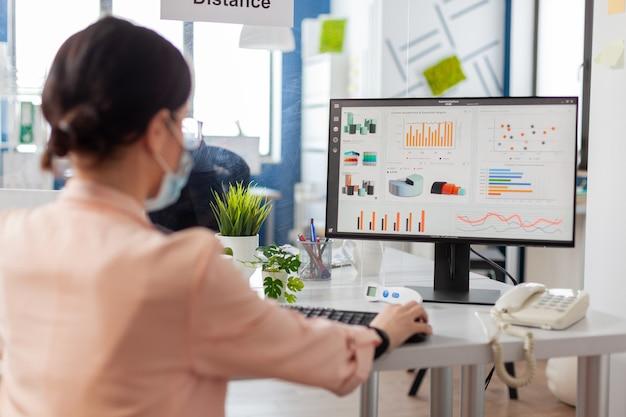 Женщина в финансовой компании в маске смотрит на статистику, графики в качестве профилактики во время глобальной вспышки гриппа covid19. безопасность между коллегами была разделена.