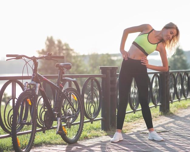 Женщина в фитнес-одежде делает разминку