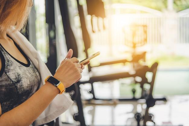 スマートフォンを使用してフィットネスの服の女性。運動用のジムで