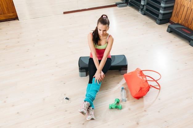 Женщина в спортивной фитнес-одежде, сидя в тренажерном зале
