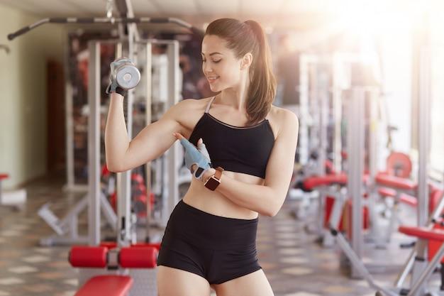 彼女の上腕二頭筋を示すフィットネスウェアの女性。ジムでのトレーニング中に彼女の腕を見て、壁にフィットネスステーションでポーズをとっている女性が彼女の結果を誇りに思っているフィットネス女性。