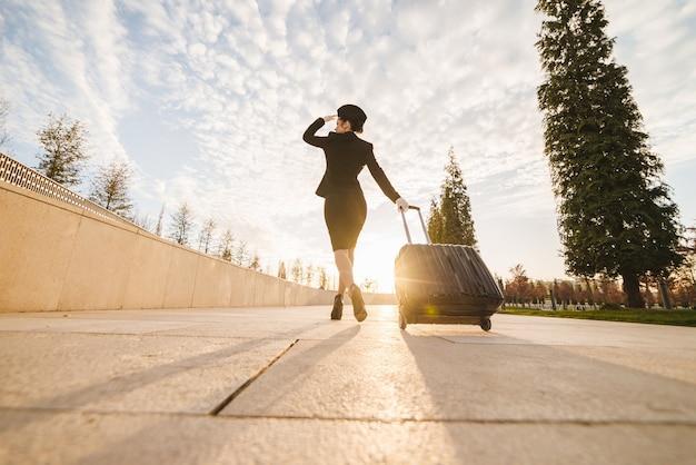 客室乗務員の女性がスーツケースを運ぶ