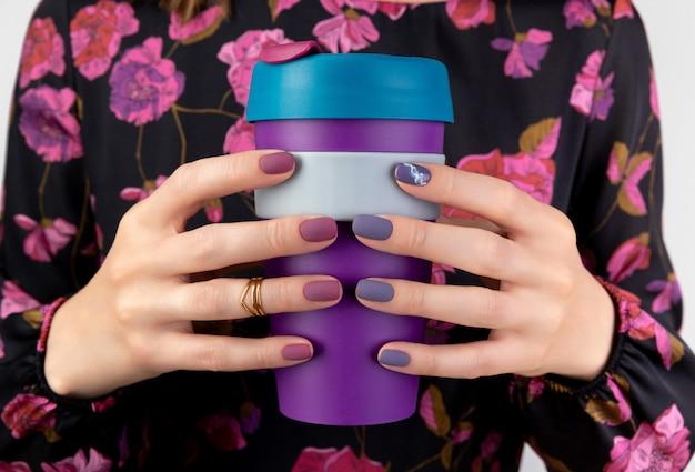 꽃 패턴 드레스에 여자는 재사용 가능한 컵을 보유하고 있습니다.