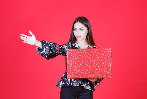 白い点が付いた赤いギフトボックスを持って、誰かにそれを提示するように誘う花柄のシャツを着た女性。