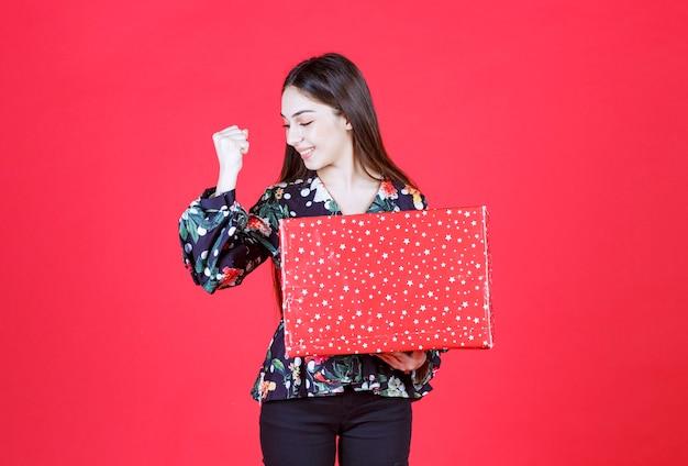 흰색 점이 있는 빨간색 선물 상자를 들고 긍정적인 손 기호를 보여주는 꽃 셔츠에 아름 다운 여자.