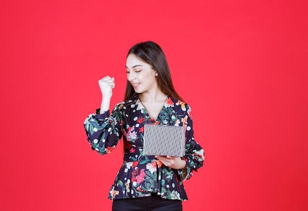 銀のギフトボックスを保持し、肯定的な手のサインを示す花柄のシャツの女性。
