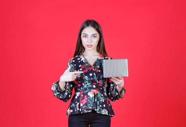 銀のギフトボックスを保持している花柄のシャツの女性。