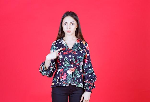 Женщина в цветочной рубашке, стоя на красной стене и представляя себя.