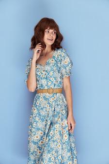 花のドレスの女性ファッショナブルな髪型の手に髪を持って笑顔を脇に見てください