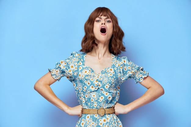 花のドレスの女性口を開けて、ベルトのファッショナブルな髪型の夏服を手に
