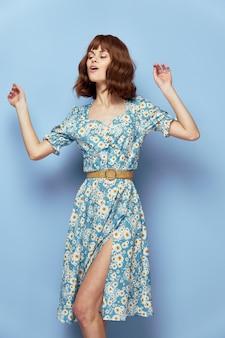花のドレスの女性目を閉じて、彼の顔の近くに手を握ってスタイリッシュな服青い背景