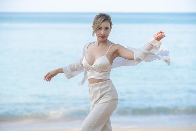 空飛ぶシャツを着た女性が海とビーチを歩きます。