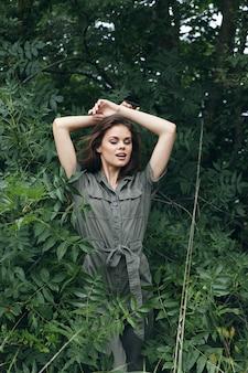 森の中の女性頭上に腕を組んでジャンプスーツ自然クロップドビュー
