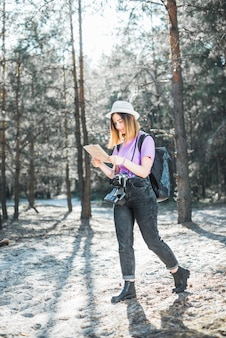 Woman in forest reading map