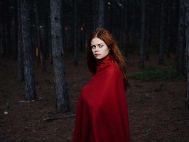 赤い格子縞の旅行ポーズと森の女性