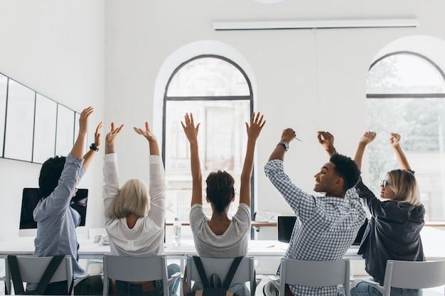 大きな光の会議場で同僚の間に座って、手を振っているブロンドの髪のフォーマルなシャツの女性。オフィスでの会議中にストレッチしている疲れたマネージャーの後ろからの写真。