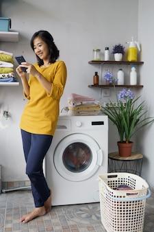 洗濯機の前にいる女性が、電話中に洗濯物を中に入れて洗濯をしている