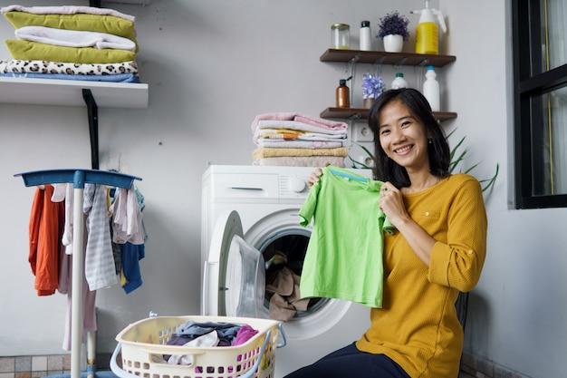洗濯機の前で洗濯物を入れている女性