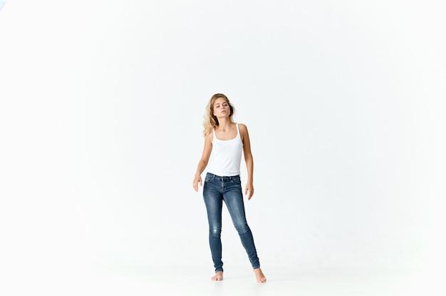 ジーンズとtシャツモデルの明るい背景で完全に成長している女性。高品質の写真