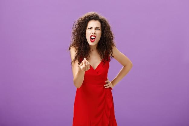 남편과 돈을 놓고 싸우는 분노에 휩싸인 여성은 빨간색 우아한 드레스를 입은 보라색 벽에 불쾌하고 화난 분노와 분노로 인해 손가락으로 이탈리아 제스처를 하고 있습니다.