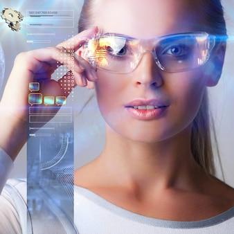 미래형 안경을 쓴 여성이 추상 홀로그래픽 데이터로 작업합니다.